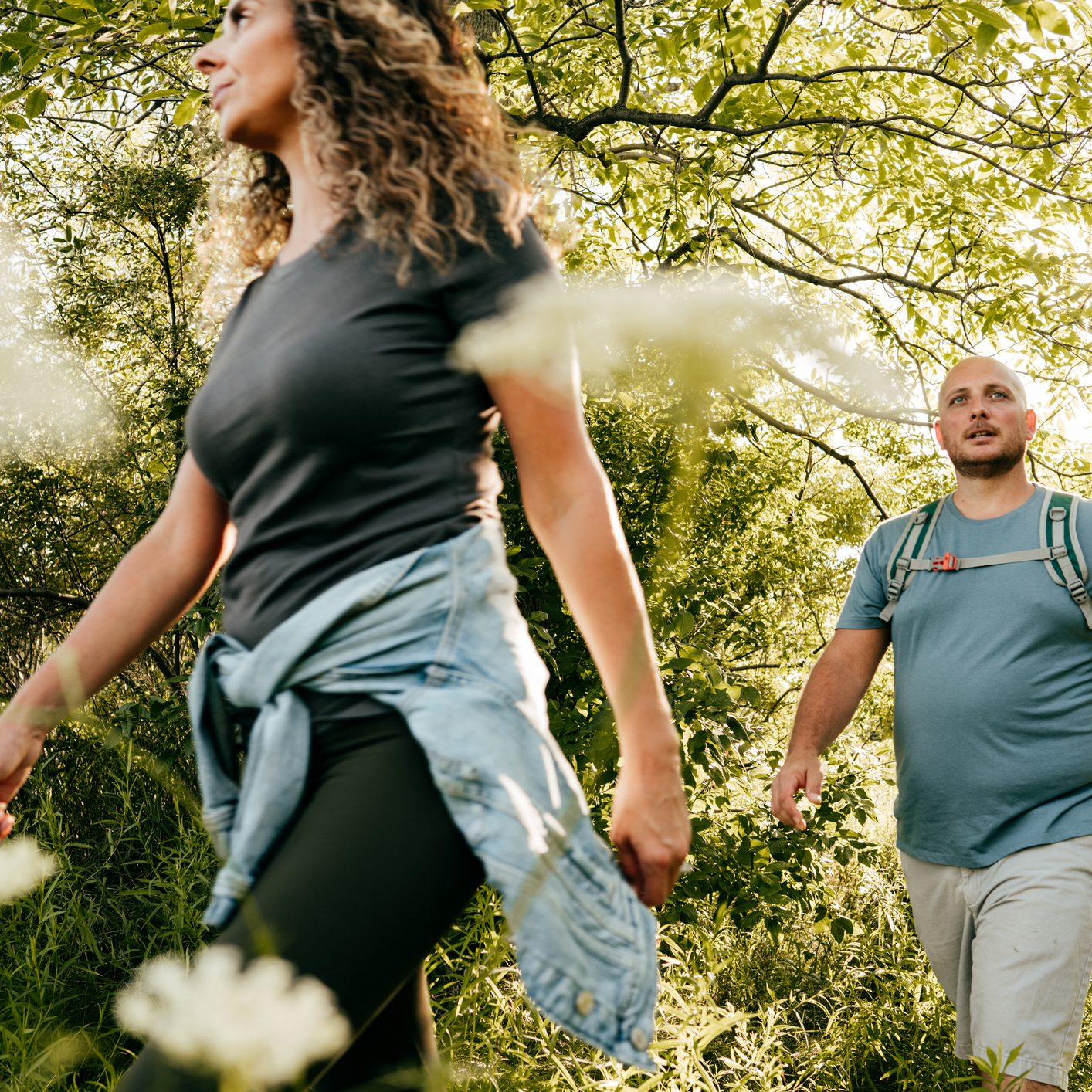 Caucasian couple walking in the park. Young woman and overweight man walking through the woods.