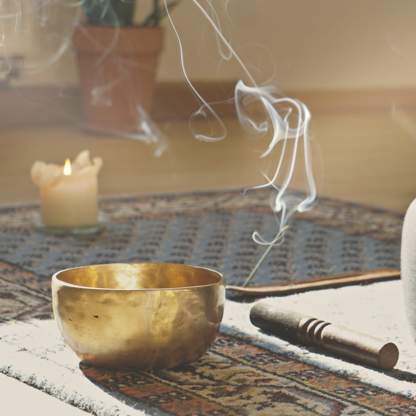 meditation room with singing bowl, incense stick, smoke, pillow and candle